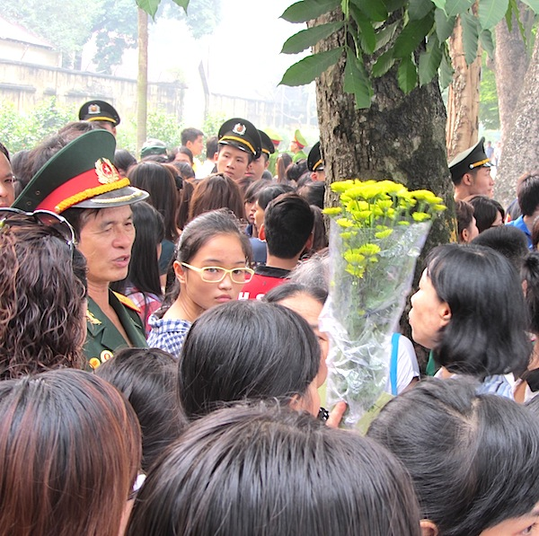 A woman tries to hand over chrysanthemum flowers to an officer for placing with other wreaths in Hanoi Sunday.