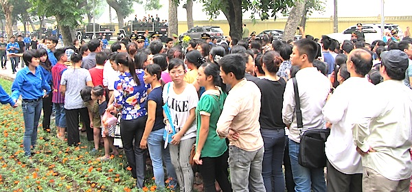 Crowds press in to try and see the funeral procession in Hanoi Sunday.