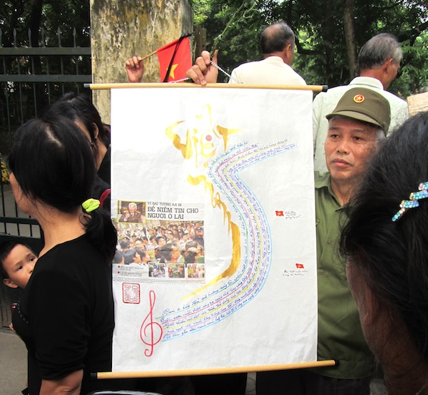 An officer holds a poster commemorating General Giap on Hoang Dieu, Hanoi on Sunday.